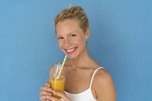 Smiling blond woman drinking juice, blue background - JOSF03577