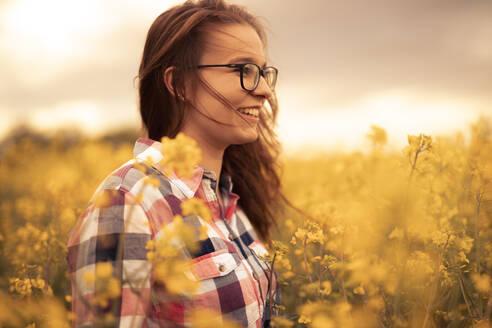 Feldweg, Deutschland, Baden-Württemberg, Nürtingen, junge Frau mit Brille lächelnd in einem blühenden Rapsfeld, Freude und Zufriedenheit - SEBF00110
