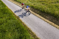 Triathletes riding bicycle on country road, Germany - STSF02142