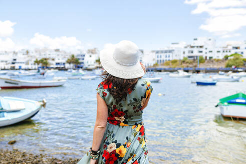 Rear view of woman with white sun hat at harbour in Arrecife, Spain - KIJF02518