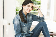 Portrait of smiling young woman wearing denim shirt at home - UUF18264