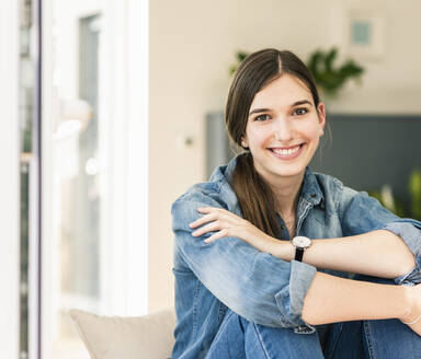 Portrait of smiling young woman wearing denim shirt at home - UUF18267
