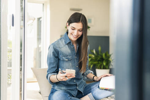 Smiling young woman checking cell phone at home - UUF18270