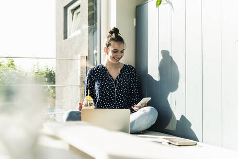 Smiling young woman with laptop, cell phone and healthy drink at home - UUF18273