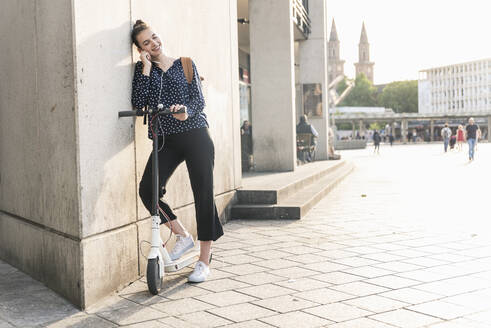 Smiling young woman with electric scooter and earphones having a break in the city - UUF18294