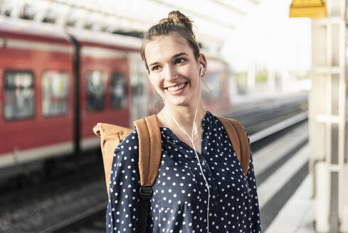 Portrait of smiling young woman at the train station - UUF18297