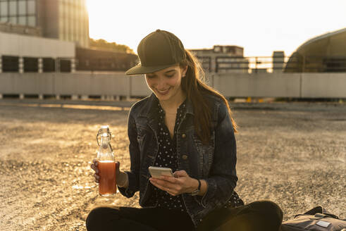 Smiling young woman with drink and cell phone sitting on parking deck at sunset - UUF18312