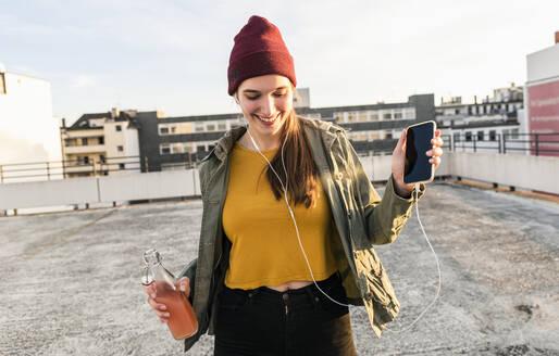 Happy young woman with earphones dancing on parking deck - UUF18327