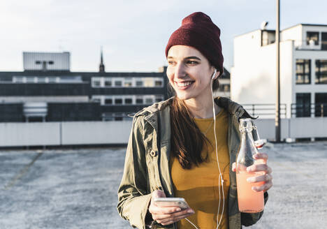 Smiling young woman with drink, earphones and cell phone on parking deck - UUF18333