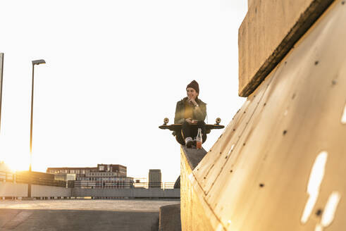 Stylish young woman with skateboard on parking deck - UUF18336
