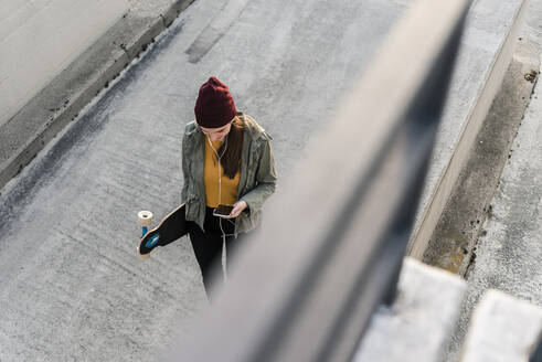 Stylish young woman with skateboard and cell phone on parking deck - UUF18342