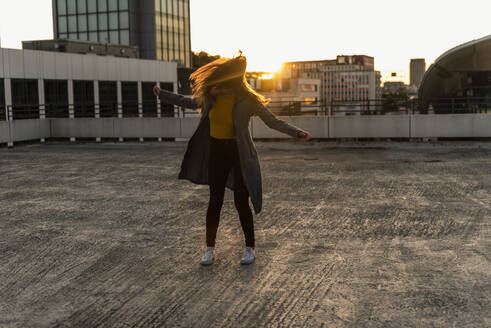 Cheerful young woman dancing on parking deck at sunset - UUF18345