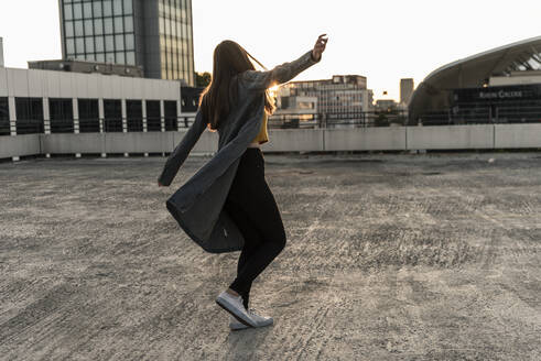 Cheerful young woman dancing on parking deck at sunset - UUF18348