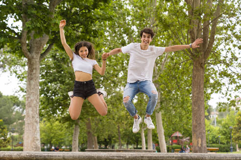 Young couple jumping from a wall at the park - MGIF00640
