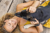 Husky shepherd mongrel dog and his mistress lying on wooden board - TCF06150