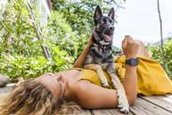 Husky shepherd mongrel dog and his mistress lying on wooden board - TCF06153