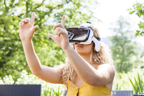 Young blond woman using virtual reality glasses outdoors - TCF06159