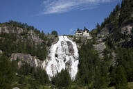Building over waterfall on remote hillside - BLEF12054