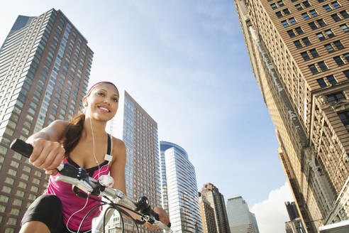 Hispanic woman riding bicycle under highrise buildings - BLEF12078