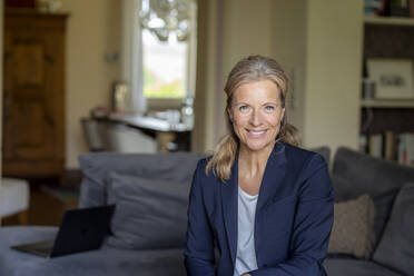 Portrait of smiling mature businesswoman at home - FMKF05747