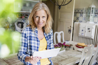 Portrait of smiling mature woman with digital tablet in the kitchen - FMKF05753