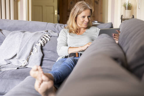 Smiling blond woman relaxing on couch at home using digital tablet - FMKF05756