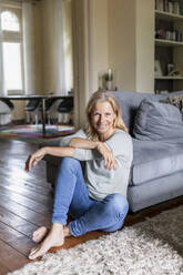Portrait of smiling mature woman siiting barefoot on the floor in the living room - FMKF05759