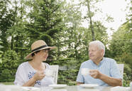 Senior couple drinking coffee in the garden looking at each other - AHSF00691