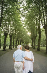 Back view of senior couple strolling  in a park at sunset - AHSF00694