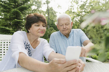Portrait of senior couple sitting at garden table looking at cell phone - AHSF00706