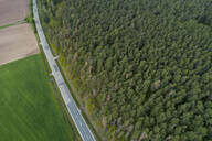 Aerial view of road between forest and agricultural fields, Franconia, Bavaria, Germany - RUEF02271