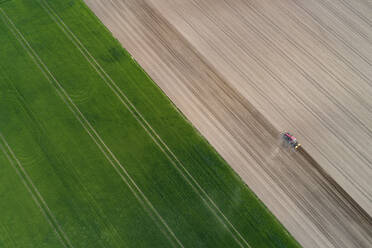 Aerial view of tractor in agricultural field, Franconia, Bavaria, Germany - RUEF02274
