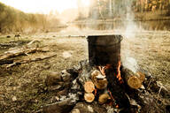 Pot cooking on campfire in rural field - BLEF12090