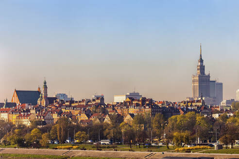 Poland, Warsaw, city skyline with Old Town houses and Palace of Culture and Science - ABOF00436