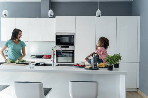 Happy mother and daughter cooking in kitchen together - ERRF01672