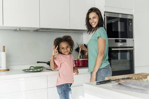 Happy mother and daughter cooking in kitchen together - ERRF01678