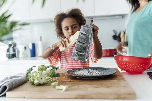 Girl cooking with mother in kitchen grating cheese - ERRF01684