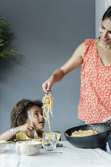 Mother serving pasta meal for daughter sitting at dining table - ERRF01717
