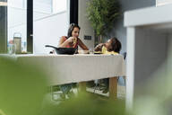 Mother and daughter eating pasta at dining table - ERRF01720