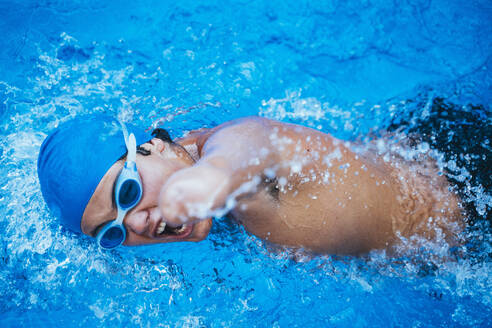 Side view of paralympic sportsman in goggles and cap without hand swimming crawl style in pool - JCMF00078