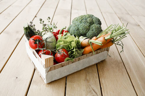 Wooden box of organic vegetables on wooden floor - KMKF01018