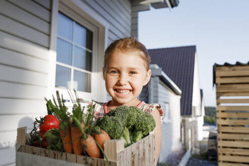 Portrait of happy little girl with wooden box of organic vegetables - KMKF01021