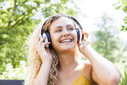 Smiling woman listening to music outdoor - TCF06173
