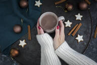 Woman's hands holding cup of Hot Chocolate at Christmas time - JUNF01694