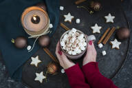 Woman's hands holding cup of Hot Chocolate with marshmellows at Christmas time - JUNF01697