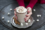 Woman's hands holding cup of Hot Chocolate with marshmellows - JUNF01703
