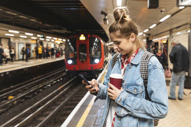 Young woman at subway station using a smartphone - WPEF01631