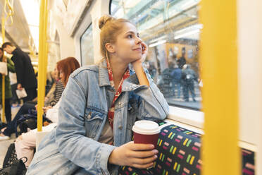 Young woman travelling by train and looking out of the window - WPEF01634