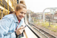 Happy young woman with smartphone travelling by train - WPEF01637