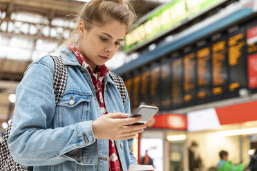 Young woman checking smartphone at the train station - WPEF01646